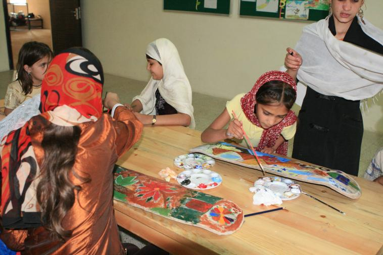 Girls painting on skateboards at Skateistan Afghanistan